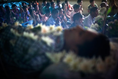 Mourners, seen through a net covering the deceased, chant Buddhist verses during the funeral for Kyaw Naing Aung