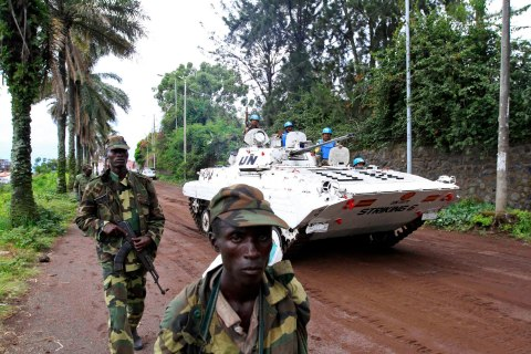 U.N. peacekeepers' armoured vehicle drives past CRA rebels patrolling a street in Goma, soon after capturing the city from the government army