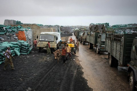 image: Somali youths pull donkey-drawn water carts past sacks of charcoal by the roadside as a convoy of the African Union Mission in Somalia soldiers of the Kenyan Contingent makes its way through the city of Kismayo, Oct. 2, 2012.