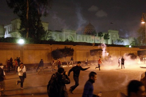 image: Egyptian protesters run away from tear gas as they were removing barriers outside of the presidential palace in Cairo, Dec. 4, 2012.