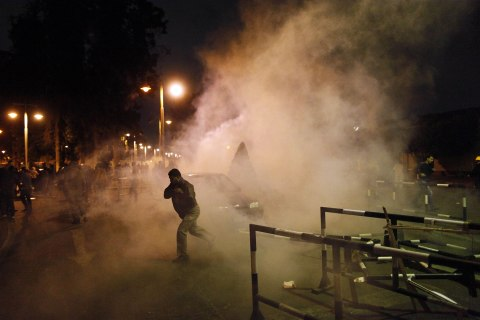 image: Protesters run away from tear gas as they try to remove barriers from outside the Egyptian presidential palace's main gate during a demonstration in Cairo on Dec. 4, 2012.