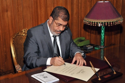 image: An image released by the Egyptian Presidency shows President Mohamed Morsi at his office in the presidential palace in Cairo on Dec. 26, 2012, as he signs a new constitution.