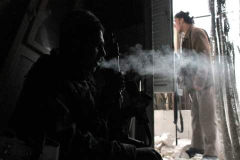 A Free Syrian Army fighter smokes as he takes a break in Aleppo