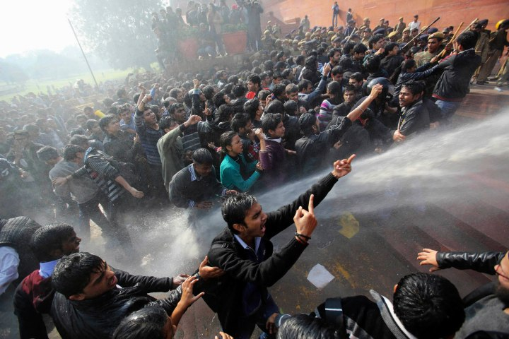 image: Demonstrators shout slogans as police use water cannons to disperse  the crowd near the presidential palace during a rally in New Delhi, Dec. 22, 2012.