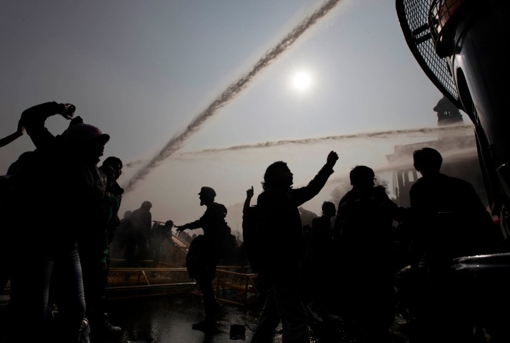 image: Protesters shout slogans as they break a police barricade after police used water cannons to disperse the crowd during  protests in New Delhi, Dec. 22, 2012.