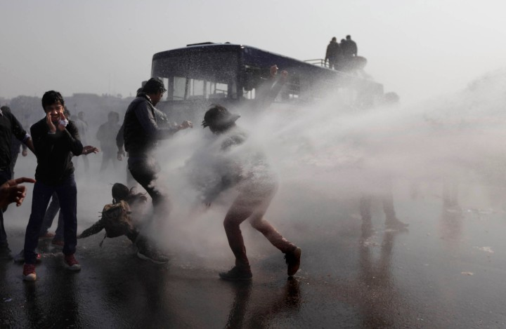 image: Indian policemen use water canon to disperse protesters during a march towards the Presidential Palace in New Delhi, India, Dec. 22, 2012.