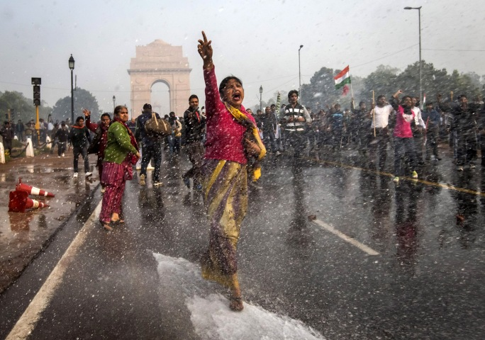 image: A protestors chants slogans as she braces herself against the spray fired from police water canons during a protest against the Indian government's reaction to the recent rape, New Delhi, Dec. 23, 2012.
