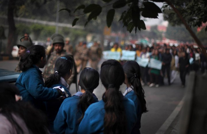 image: A group of school girls watch as protesters demonstrate against the brutal gang-rape of a woman on a moving bus New Delhi, India, Dec. 24, 2012.