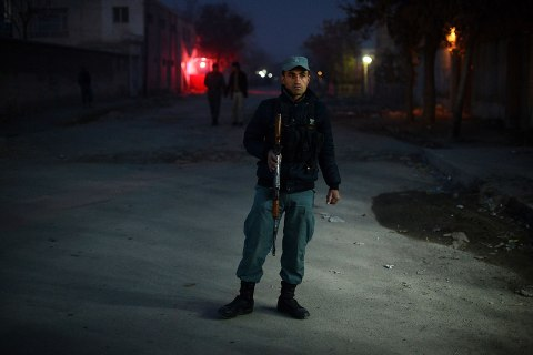 image: An Afghan policeman stands guard near the site of a Taliban sucide bomber attack at a spy agency guesthouse in Kabul, Dec. 6, 2012.