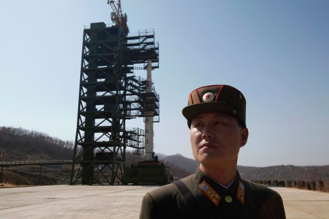 image: A soldier stands guard in front of a rocket sitting on a launch pad at the West Sea Satellite Launch Site, during a guided media tour by North Korean authorities in the northwest of Pyongyang, April 8, 2012.