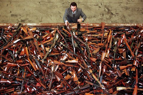 image: Mick Roelandts, firearms reform project manager for the New South Wales Police, looks at a pile of about 4,500 prohibited firearms in Sydney that have been handed in over the past month under the Australian government's buy-back scheme, July 28, 1997.