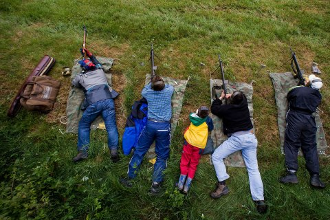 image: Swiss marksmen shoot with their rifles at targets over 300 metres away in a field during the 'Eidgenoessisches Feldschiessen' (annual shooting skills exercise) on the Aeschlenalp near Bern, June 6, 2009.