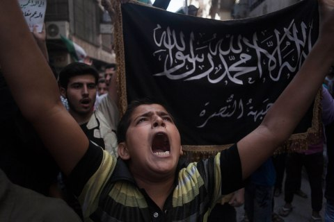 image: A Syrian shouts slogans against the regime in front of a flag of the armed Islamic opposition group al-Nusra front during a demonstration in the Bustan al-Qasr neighborhood of Aleppo, Sept. 21, 2012.