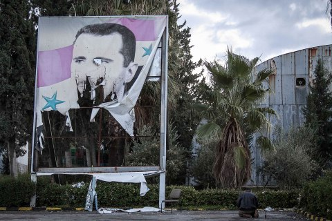 image: A Free Syrian Army fighter offers evening prayers beside a damaged poster of Syria's President Bashar Assad during heavy clashes with government forces in Aleppo, Dec. 8, 2012.