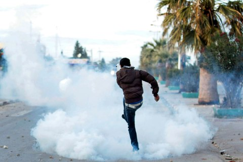 image: A protester kicks a tear gas canister back at police during clashes in Siliana, northwest of Tunis, Dec. 1, 2012.