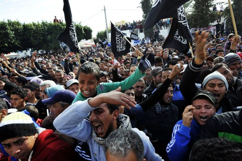 image: Inhabitants of Sidi Bouzid wave black religious flags and shout slogans calling for Tunisia's President Moncef Marzouki to leave in Sidi Bouzid, Dec. 17, 2012.