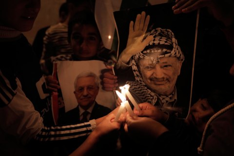 image: Palestinian children hold a poster of the late president Yasser Arafat and candles as they take part in a candle lit vigil in Balata refugee camp near the West Bank city fo Nablus, Nov. 28, 2012.