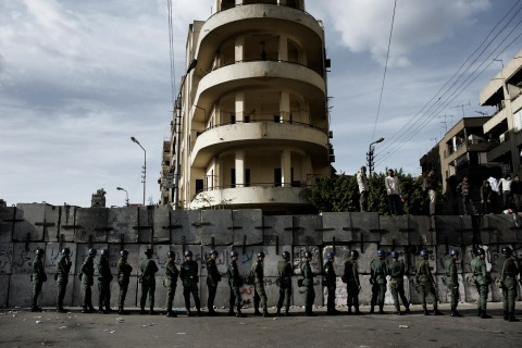 image: Members of the Republican Guard stand behind a wall erected to block a road that anti-Morsi protesters are trying to use to reach the presidential palace, on Dec. 11, 2012.