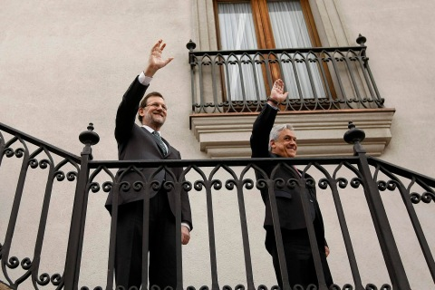 Chile's President Pinera and Spain's PM Rajoy wave to the media at the La Moneda Presidential Palace in Santiago