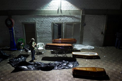 A man stands around coffins containing the remains of victims after the bodies were identified at a gymnasium in Santa Maria city, Brazil, Jan. 27, 2013.