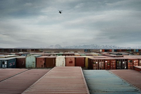 A helicopter flies over hundreds of containers full of equipment stacked in the yards of Forward Operating Base Shank, the logistical hub for American operations in Logar Province, Afghanistan, Jan. 27, 2013.