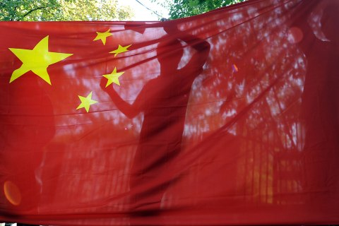 The silhouette of a demonstrator is seen behind a flag of the People's Republic of China during a protest over disputed islands in the East China Sea at the Japanese Embassy in Budapest, Sept. 24, 2012.