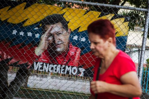 image: A woman walks next to a graffit painting of Venezuelan president Hugo Chavez in Caracas, Venezuela, on Jan. 2, 2013.