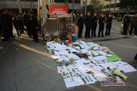 image: Security guards stand near protest banners and flowers laid outside the headquarters of Southern Weekly newspaper in Guangzhou, Guangdong province, China, Jan. 7, 2013.