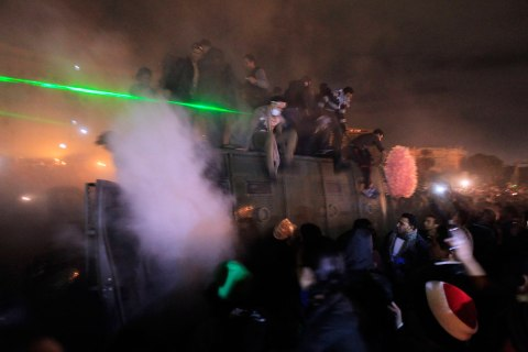 Anti-Morsi protesters stand on a riot police vehicle after they seized it on the Kasr Elnile bridge to Tahrir square in Cairo, Jan. 28, 2013.