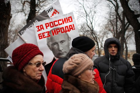"image: People carry posters of Russian President Vladimir Putin with the words reading ""For Russia without Herod!"" during a protest rally against the adoption ban in Moscow, Jan. 13, 2013."