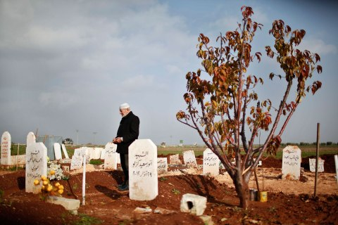 image: Abdlhamid Haj Omar, 70, a father who lost three sons and two grandsons in the ongoing Syrian crisis, prays as he visits their graves at the Martyrs' cemetery in Azaz city, North Aleppo, Dec. 25, 2012.