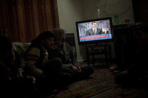 image: Rebel fighter sit watching Syrian President Bashar al-Assad making a public address on the state-run Syrian TV in Aleppo, Jan. 6, 2013.