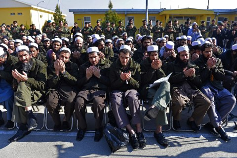 image: Released Taliban prisoners sit on chairs and pray during a ceremony in Pul-e-Charkhi jail while Afghanistan National Army soldiers look, Jan. 4, 2013.