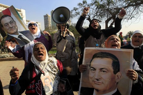 Supporters of Egypt's deposed president Mubarak hold up his pictures as they celebrate outside the Maadi Armed Forces hospital, where Mubarak is currently being held, in Cairo