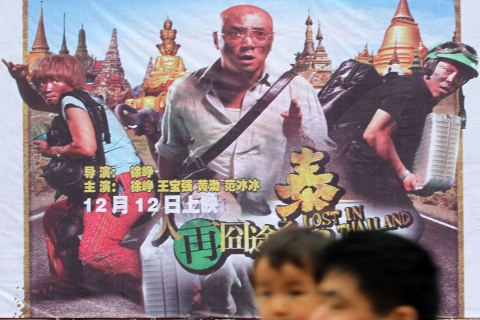 "image: Pedestrians walk past a poster of the movie, ""Lost in Thailand,"" at a cinema in Nantong city, China, Dec. 16, 2012."