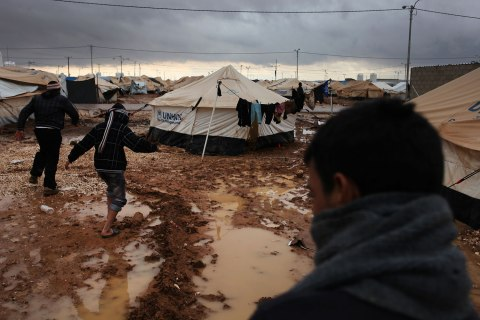 image: Syrian refugees make their way on water and mud, at Zaatari Syrian refugee camp, near the Syrian border in Mafraq, Jordan, Jan. 8, 2013.