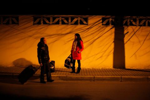 Li Anhua and his wife Shi Huaju wait for a taxi as they start their annual trip for Spring Festival in Shanghai on Jan. 27, 2013.