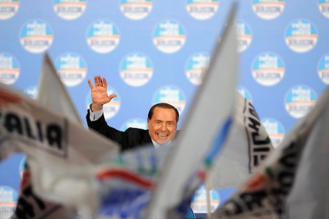 Former Italian Prime Minister Silvio Berlusconi waves to supporters during a political rally in Turin