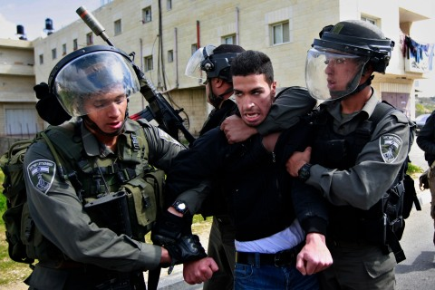Isreali border policemen arrest a Palestinian man during a protest to support Palestinian prisoners, outside Ofer, an Israeli military prison near the West Bank city of Ramallah on Feb. 28, 2013.