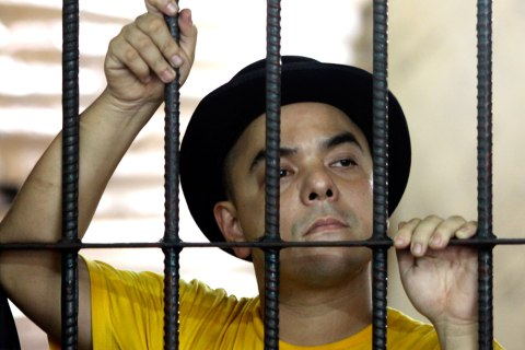 Carlos Celdran holds on prison bars inside the detention cell in Manila,, Oct. 1, 2010.