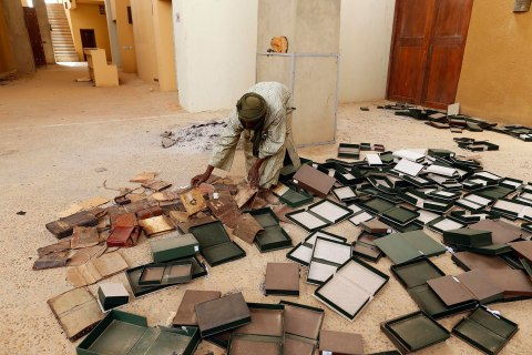 A museum guard picks up boxes holding ancient manuscripts, which were partially damaged by Islamist rebels, at the Ahmed Baba Institute in Timbuktu Jan. 31, 2013.