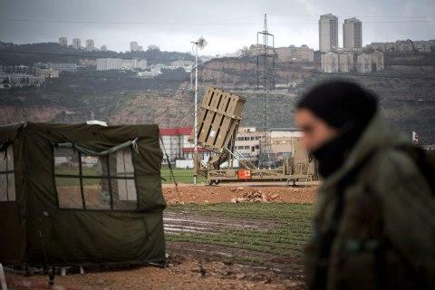 An Israeli soldier walks by an 'Iron Dome' short-range missile defense system positioned near the northern city of Haifa on Jan. 31, 2013 in Israel. The Iron Dome missile defense system is designed to intercept and destroy incoming short-range rockets and artillery shells.