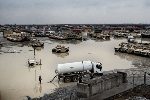 Civilian contractors work to drain a large puddle following a winter rain at Bagram Airbase, Afghanistan, Jan. 31, 2013.