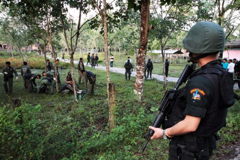Security personnel investigate around bodies of insurgents at the site of an attack on an army base in the southern province of Narathiwat