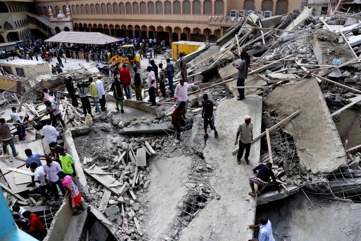 Rescuers search for survivors amongst a collapsed building in the Kariakoo district of central Dar es Salaam