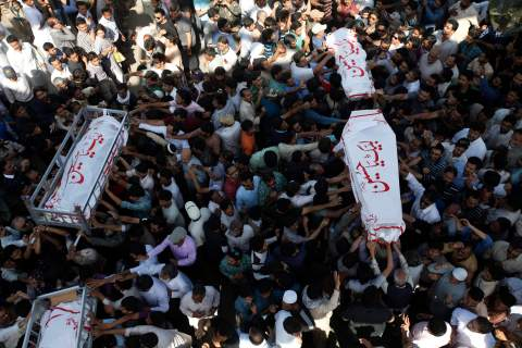 Shi'ite Muslims carry bodies of victims, who were killed in bomb attack a day earlier, after a funeral prayer in Karachi