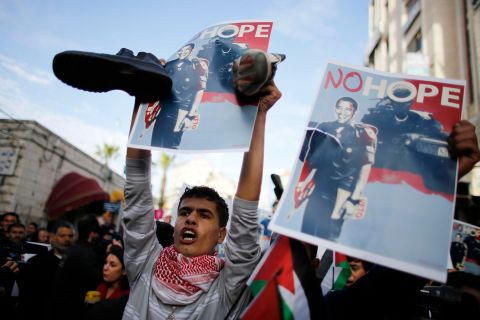 A Palestinian demonstrator holds shoes and a digitally manipulated placard depicting U.S. President Obama during a protest in Ramallah.