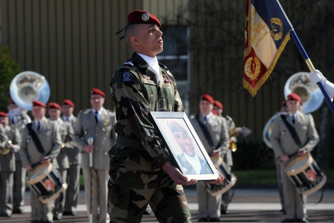 A soldier holds a portrait of late French paratrooper Imad Ibn Ziaten, the first victim of Islamist gunman Mohamed Merah, on March 11, 2013 in Toulouse, during a ceremony awarding him with the Legion d'Honneur.