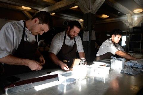 Cooks prepare some dishes in a preparation kitchen of the Noma restaurant in Copenhagen