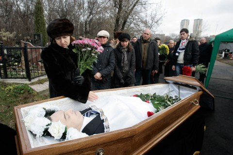 Nataliya Magnitskaya, mother of Sergei Magnitsky, grieves over her son 's body during his funeral at a cemetery in Moscow
